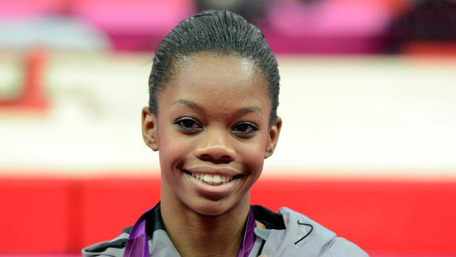 Gabrielle Douglas poses with her gold medal after winning the women's individual all-around final during the 2012 London Olympic Games at North Greenwich Arena.