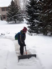 Eli shoveling snow before school.