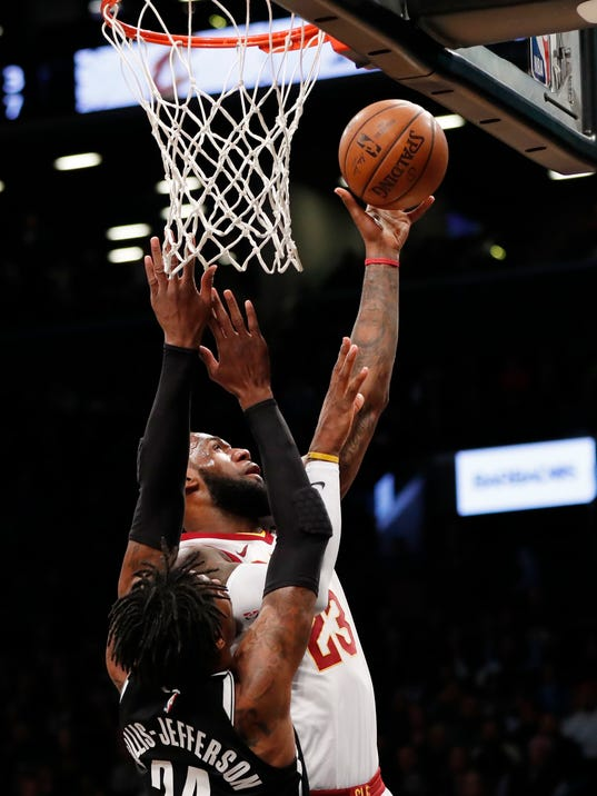 Cleveland Cavaliers forward LeBron James, right,  drives for a layup as Brooklyn Nets forward Rondae Hollis-Jefferson (24) defends during the first half of an NBA basketball game, Sunday, March 25, 2018, in New York. (AP Photo/Kathy Willens)