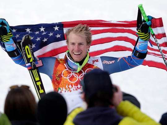 FILE - In this Feb. 19, 2014, file photo, men's giant slalom gold medalist Ted Ligety, of the United States, poses on the podium for photographers with an American flag at the Sochi 2014 Winter Olympics in Krasnaya Polyana, Russia. One might assume ski racers would be excited by the prospect of a chance to win an extra gold at the Pyeongchang Olympics thanks to the addition of a team event. Some of the sport's top stars have pretty much ruled out any chance they'll take part in the last event on the Alpine schedule. (AP Photo/Charles Krupa, File)