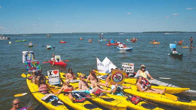Kayakers gather in front of the Roland E. Powell Convention Center to advocate for clean energy and against oil and gas.