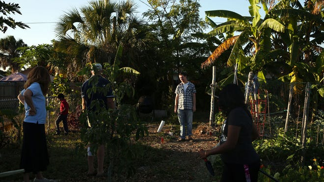 Walter Lasek Jr., 23, center, spends time with his family and neighbors in their community garden near their Naples Park home on Monday, April 18, 2016. (Dorothy Edwards/Staff)