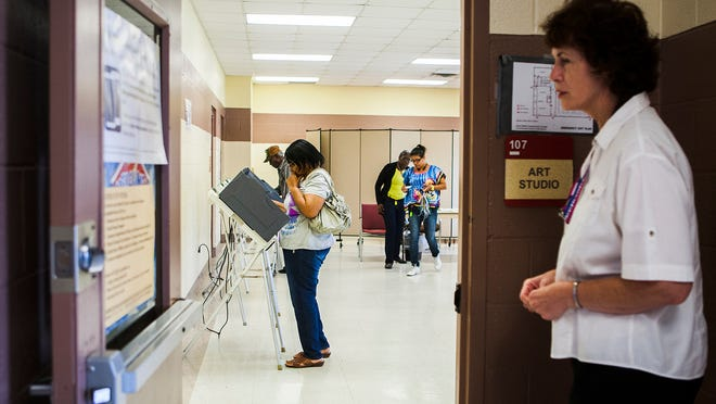September 25, 2015 - Linda-Marie Goetze (right), officer, Shelby County Election Commission, waits patiently outside a doorway of an early voting precinct, Dave Wells Community Center, for voters as Mary Wilkins (second from left) ponders a decision at a voting booth in North Memphis Friday. (Yalonda M. James/The Commercial Appeal)