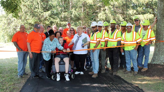 Matheny student Jacob Rolaf, assisted by personal care assistant Joan Marshall, left, and Tilcon's Chris Aaron, right, cuts the ribbon celebrating the completion of the newly paved nature trail.