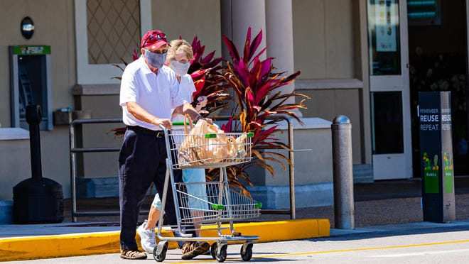 A couple wearing face masks leaves the Publix pushing a small cart with their groceries recently in Manalapan.