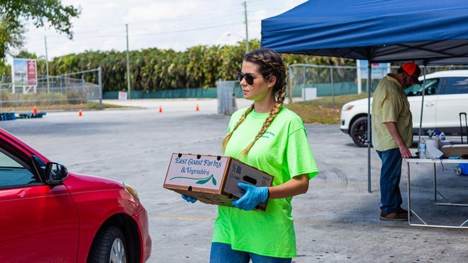 Katelyn Garcia, Director of New Business for East Coast Farms & Vegetables in Lake Worth, carries a box of vegetables to a customer's car on March 26. East Coast Farms is usually a wholesaler of farm-fresh fruits and vegetables, but for the past week, they have operated as a curbside pickup for the community. They offer $10 boxes of farm-fresh produce and a la carte items, such as melons and pineapples.