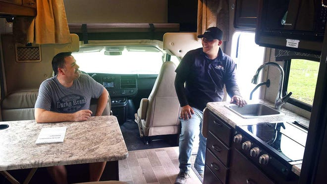 Jeff Coltenback of Wilmington, seated, discusses this 25-foot motor home on June 23 with salesman Luis Ortiz at  Riverside Camping Center. Coltenback has since put in an offer.
