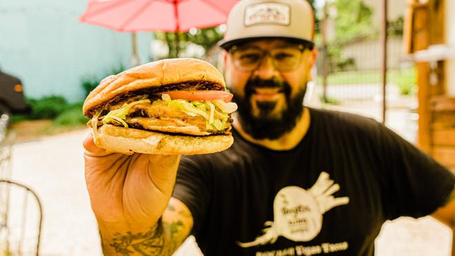 Chris Rios of Nom Burgers poses with the OG Burger. Photo courtesy of Glass Staircase.