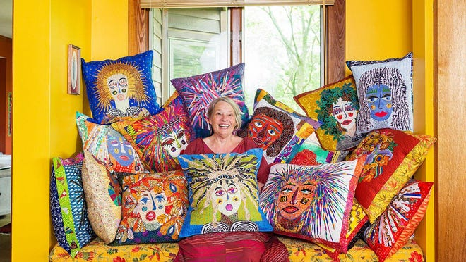 """Gina Kellogg, of Perry, sits surrounded by pillows she created as part of a yearlong project. During the past year, Kellogg would ask herself weekly """"What am I facing this week?"""" and create a face that represented what she was feeling."""