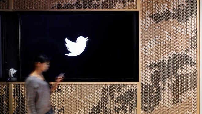 Woman walking by a Twitter logo