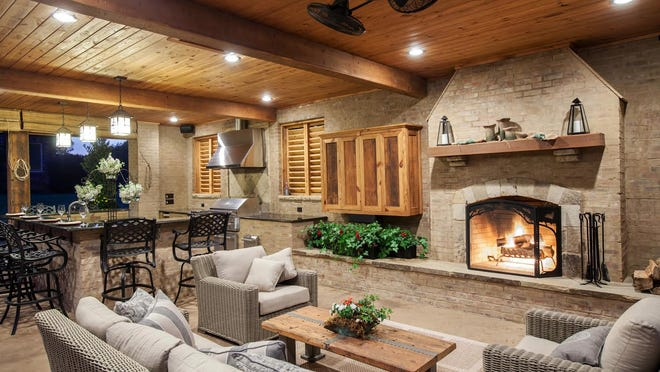 Outdoor space can be built to be useable regardless of the weather. The fireplace, built into the side of the existing house, and blinds that create a barrier against wind in the winter make the partially exposed room comfortable year-round.