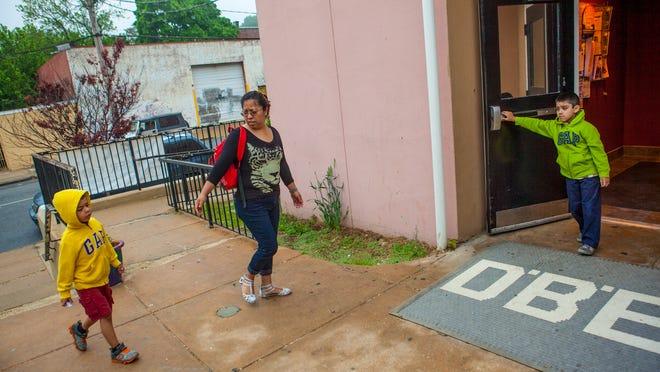 Mondzerad Gonzalez (center), arrives at the Latin American Community Center Thursday morning to drop off her children Urael (left), 5, and Jaziel, 6.