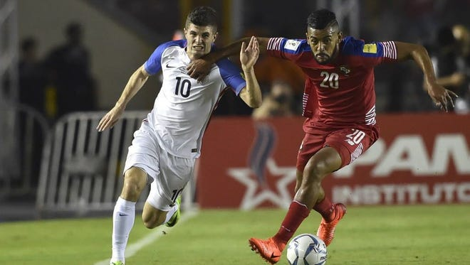 USA's Christian Pulisic and Panama's Anibal Godoy run for the ball during a World Cup qualifier in Panama City.