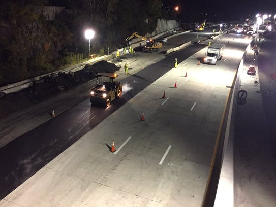 Blacktop is laid for a stretch of fourth lane being
