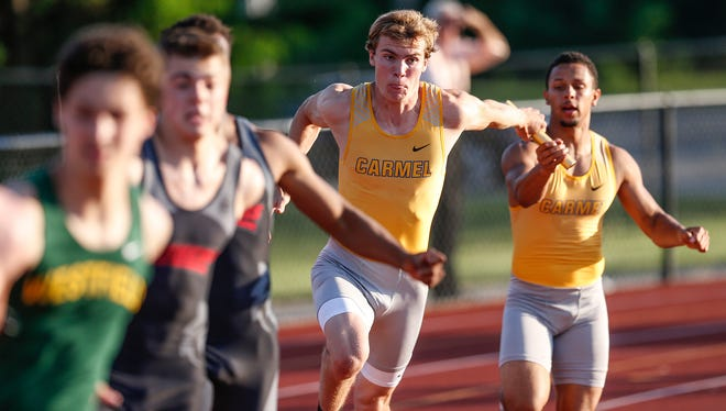 Carmel Greyhounds sprinter Ryan Lipe takes the baton during the 4x100 during the boys track and field sectional finals at Carmel High School on Thursday, May 18, 2017. Carmel would finish in first place.