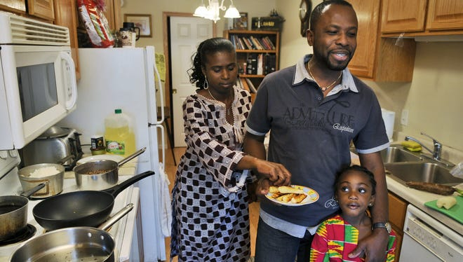 Isaac Owens in his home kitchen with his wife, Rosemond, and daughter, Hadassah.
