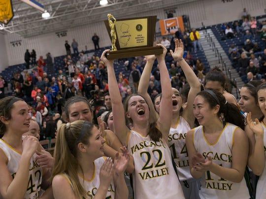 Pascack Valley's Shannon Culloo holds her team's championship trophy high as they celebreate. Pascack Valley vs Ocean City in Public Group 3 Girls Basketball Final in Toms River NJ, on March 12, 2017.