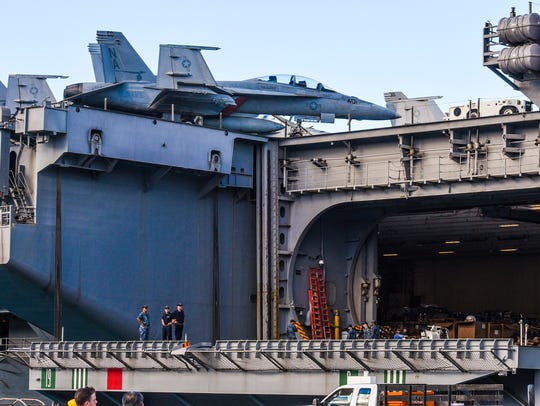 An F/A-18 Super Hornet aircraft can be seen on the deck of the Nimitz-class carrier, USS Theodore Roosevelt, while docked at the Kilo Wharf on Naval Base Guam in Sumay on Tuesday, Oct. 31, 2017.  Two men who filed a False Claims Act lawsuit against a Japanese corporation, alleging fraud in connection with a contract to extend Kilo Wharf, have been awarded $775,000.