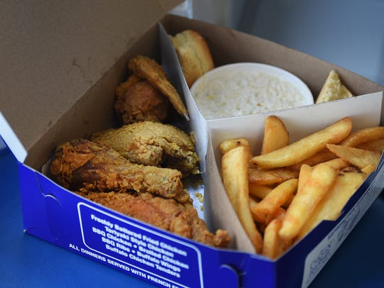 Photo of four pieces of fried chicken with side dish,