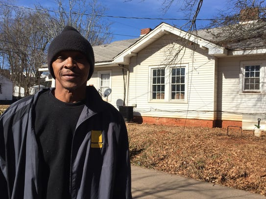 Freddy Giles stands in front of his home Wednesday,