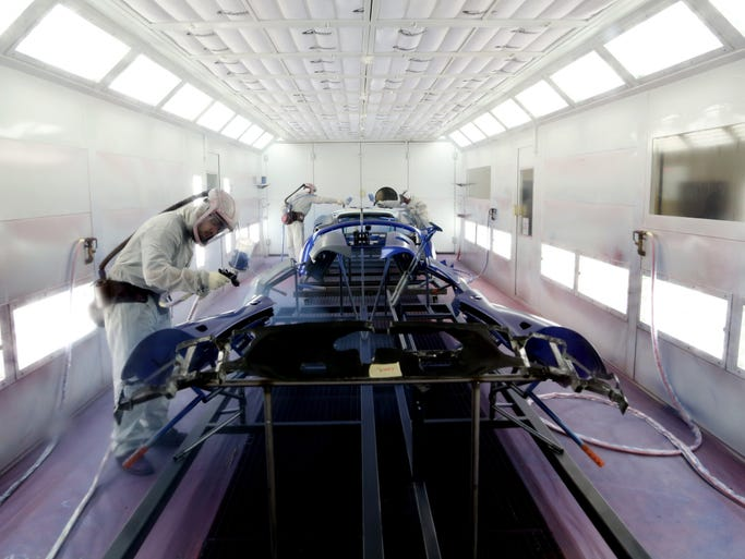 Workers at one of the 6 spray painting bays apply a coat of Viper GTS Blue paint to sides, hoods and rear paneling of the sports car.