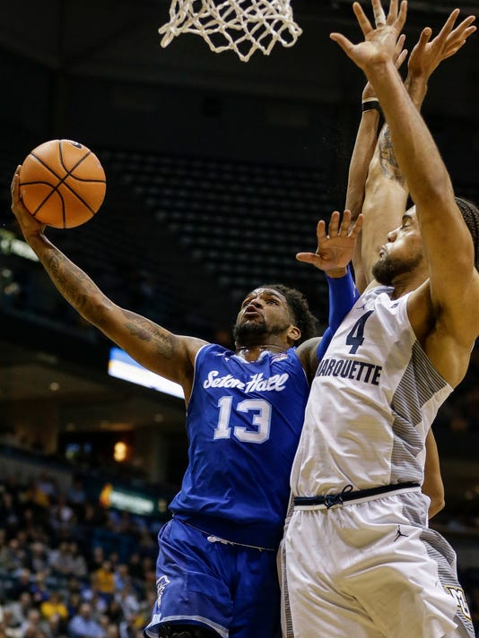 Seton Hall's Myles Powell (13) shoots the ball while being defended by Marquette's Theo John (4) during the second half of an NCAA college basketball game Tuesday, Jan. 9, 2018, in Milwaukee. (AP Photo/Tom Lynn)