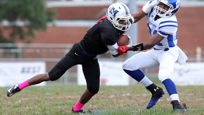 Middlesex  takes on  Metuchen in an varsity football game at  Middlesex High School.   Dennis Brodnax of Middlesex (left) fights off the tackle attempt of Metuchen's # 21 (right)- Evan Collier.   On Saturday October 18, 2014 Photo: Mark R. Sullivan/Staff Photographer