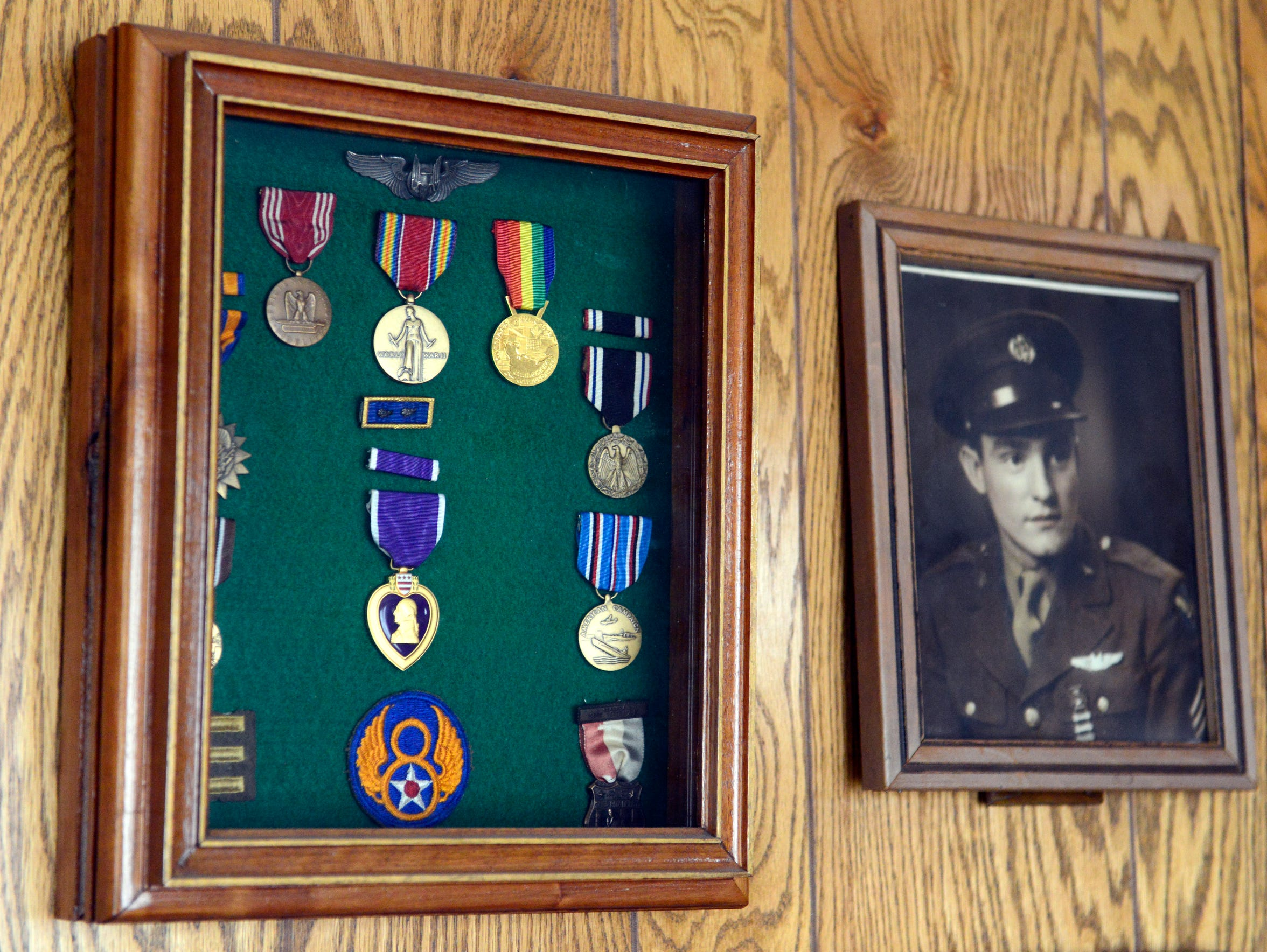 Charles Holcomb displays his metals in his home next