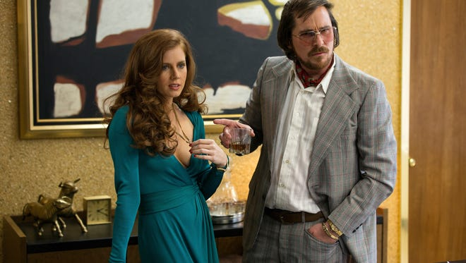 """Sydney Prosser (Amy Adams, left) and Irving Rosenfeld (Christian Bale) attempt to scam an under cover agent in a scene from the motion picture """"American Hustle."""""""