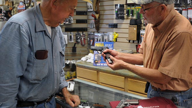 Jim Lawrence, right, manager of Texas Knifeworks and Guns, shows Keith Nylander a Colt Model 1911 pistol. The business began in 2010, but will hold a grand opening June 30 and July 1.