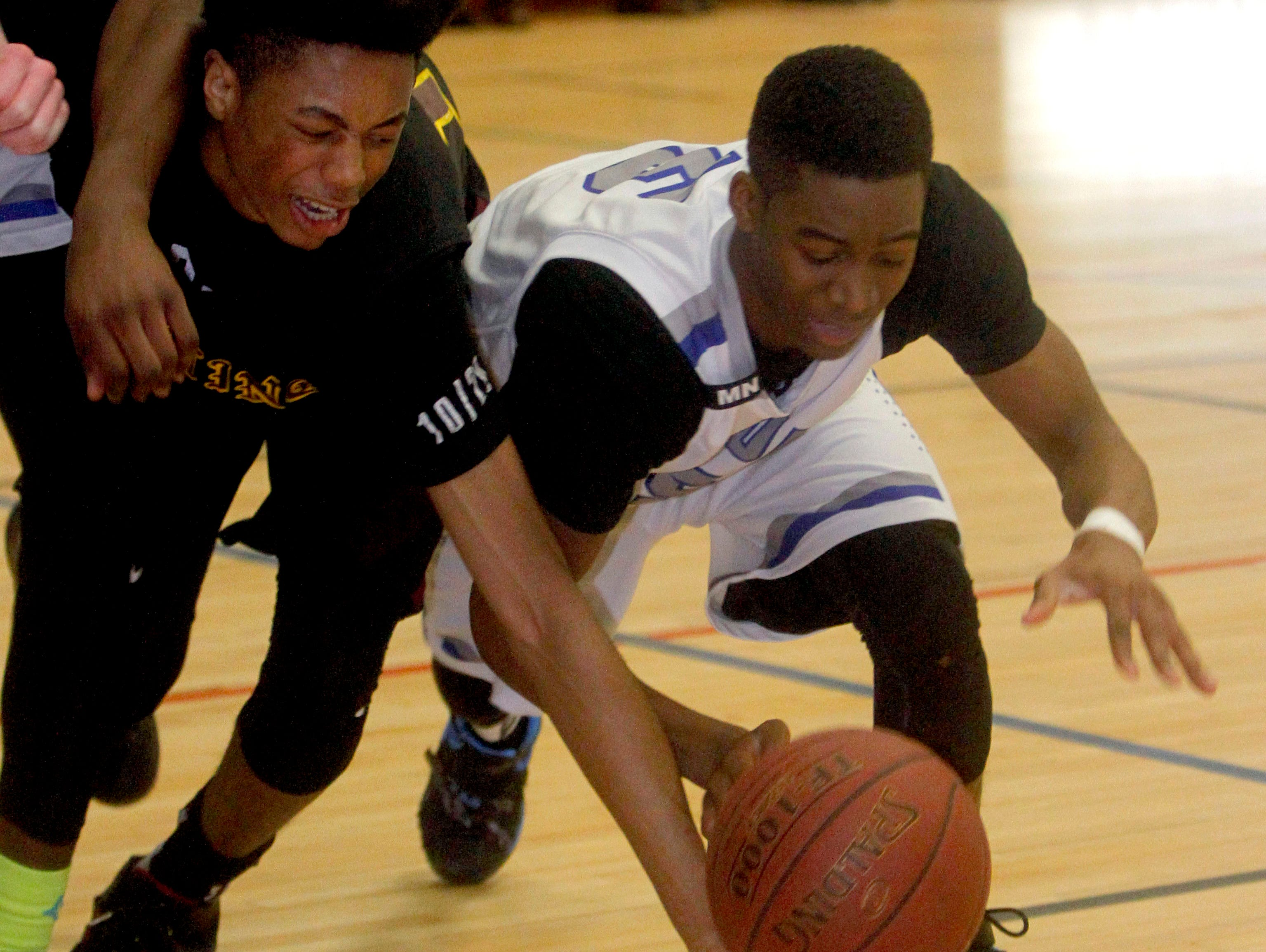 Alan Griffin of Ossining and Derrick Felder of Saunders scramble for the loose ball during the overtime period of a Class AA quarterfinal basketball game at Saunders High School Feb. 20, 2016. Saunders came from behind to defeat Ossining 54-48.