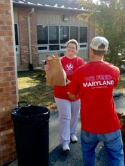 A food bank volunteer distributes a holiday meal to