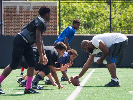 Coach Michael Hadnot of the Westside Panthers runs practice drills with his team before their game in the 10th annual Peace Bowl at the Sheakley Athletics Center Sunday July 31, 2016.