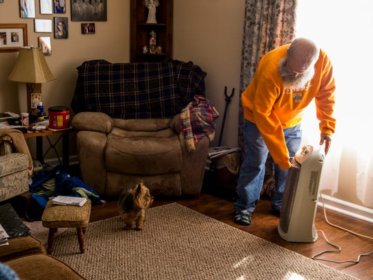David Ray, a disabled Vietnam veteran, adjusts his space heater in his home on January 17, 2018.