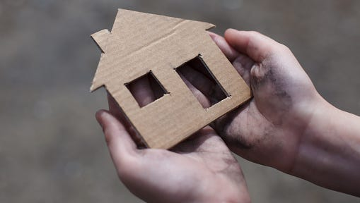 A homeless boy holds a cardboard cutout of a house.