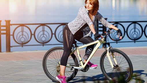 Young redhead woman riding a bike on embankment. Active people