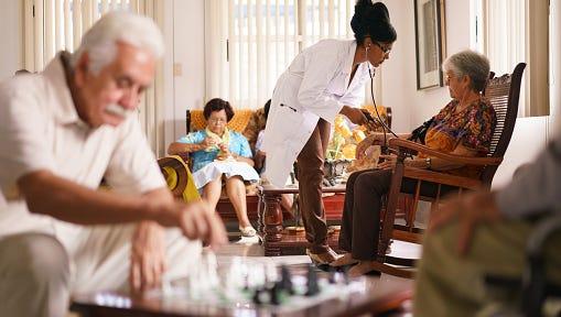Doctor Measuring Blood Pressure To Senior Woman