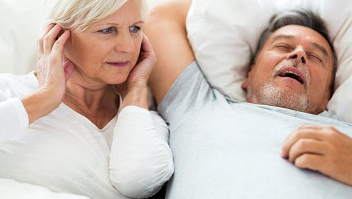 Senior man snoring and woman covering ears