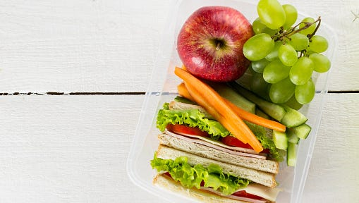 Lunchbox with sandwich, vegetables, fruit on white background