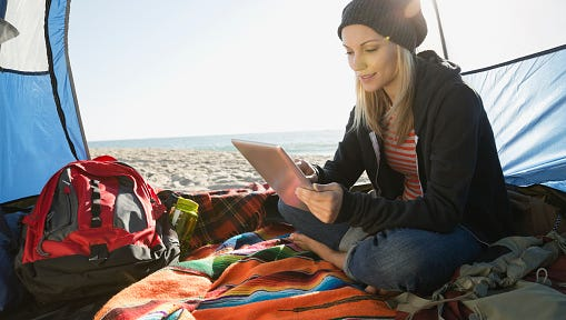 Woman using digital tablet in tent on beach