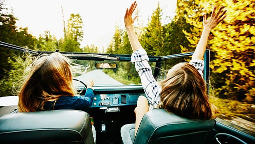 Woman riding with friend in convertible
