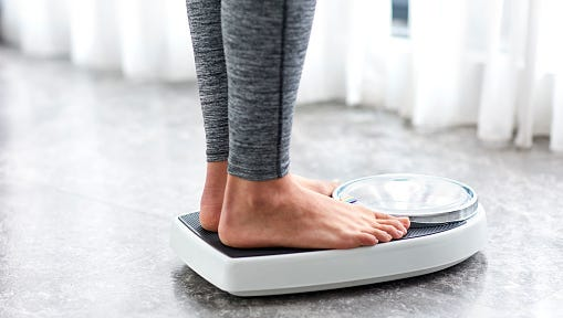 Woman weighs herself on scale