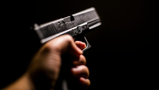 Cropped Hand Holding Gun Against Black Background