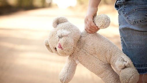 Runaway or Lost Girl Holding Old, Ragged Teddy Bear