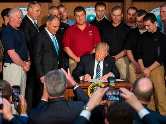 """Surrounded by miners from Rosebud Mining, US President Donald Trump signs he Energy Independence Executive Order at the Environmental Protection Agency (EPA) Headquarters in Washington, DC, March 28, 2017. President Donald Trump claimed an end to the """"war on coal"""" Tuesday, as he moved to roll back climate protections enacted by predecessor Barack Obama."""