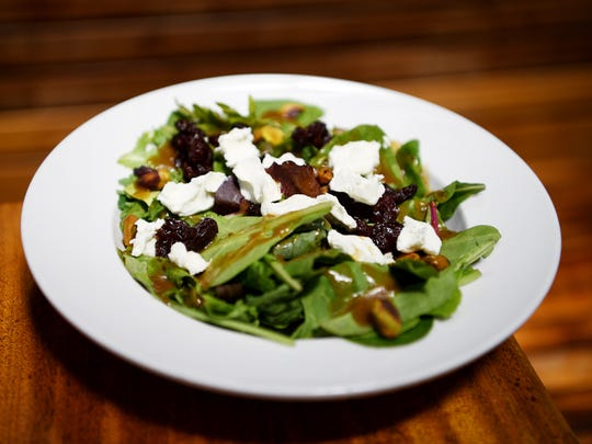 West First Wood-Fired Pizza's house salad with mixed greens tossed, roasted pistachios, sundried cherries, goat cheese and balsamic vinaigrette July 6, 2017.