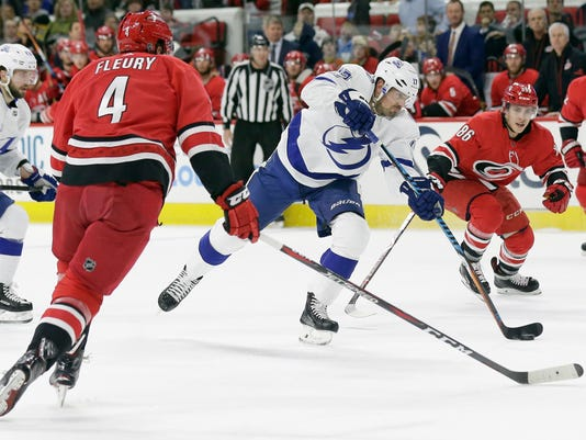 Tampa Bay Lightning's Alex Killorn (17) takes a shot while Carolina Hurricanes' Haydn Fleury (4) and Teuvo Teravainen (86), of Finland, defend during the first period of an NHL hockey game in Raleigh, N.C., Saturday, April 7, 2018. (AP Photo/Gerry Broome)