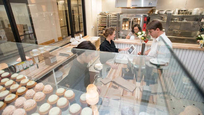 Owner Justine Gudmundson-McCain, center, rings up Dax Davault's order at Bluejay's Bakery's new location at One Palafox Place in downtown Pensacola on Thursday, November 30, 2017.