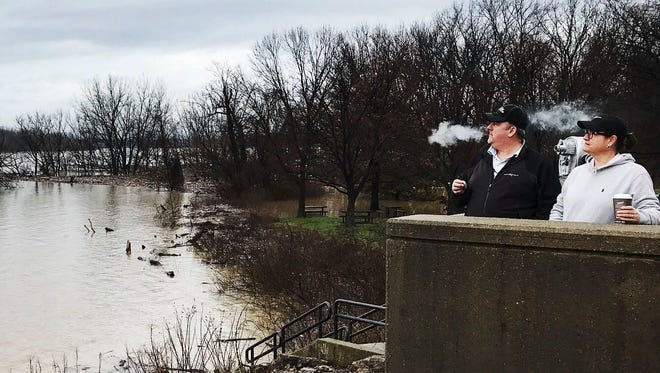 At the Falls of the Ohio, the flood covers the popular park but drew the curious who took pictures and watched as the waters silently swallowed everything in its path.