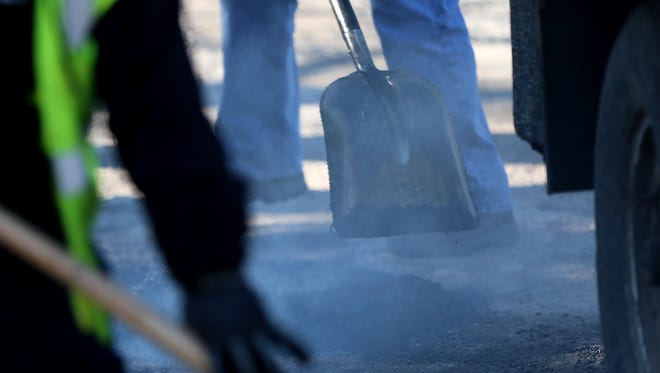 Steam rises from hot mix asphalt on the first day of an Indiana Department of Public Works (DPW) 4-day pothole blitz, near the intersection of 38th St. and Forest Manor Ave., Monday, Jan. 30, 2018.  DPW crews are using hot mix, an asphalt mix that lasts longer and adheres better.